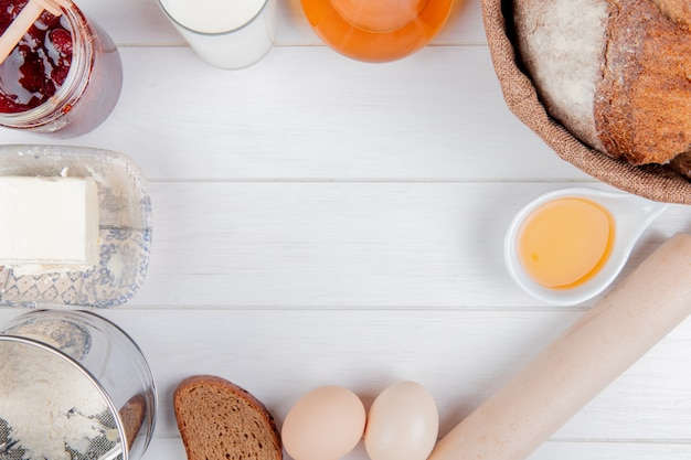 Top view of foods as strawberry jam milk butter flour cob and rye breads eggs and rolling pin on wooden background with copy space