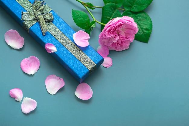 장미 꽃잎과 파란색 배경에 아버지의 날에 대 한 상위 뷰. 금색 활과 분홍색 장미가 있는 파란색 선물 상자를 닫습니다.