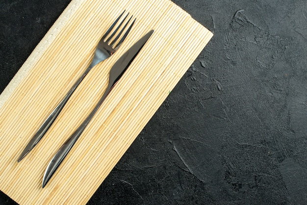 Top view fork and knife on beige wooden board on black table free space