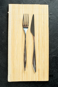 Top view fork and knife on beige wooden board on black table