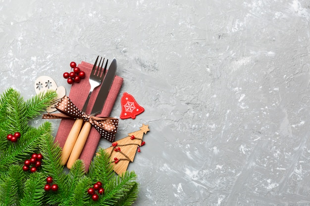 Top view of fork and knife on napkin with christmas decorations and new year tree on cement , holiday and festive concept