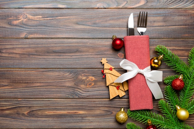 Top view of fork and knife on napkin with christmas decorations and new year tree on wooden , holiday and festive concept