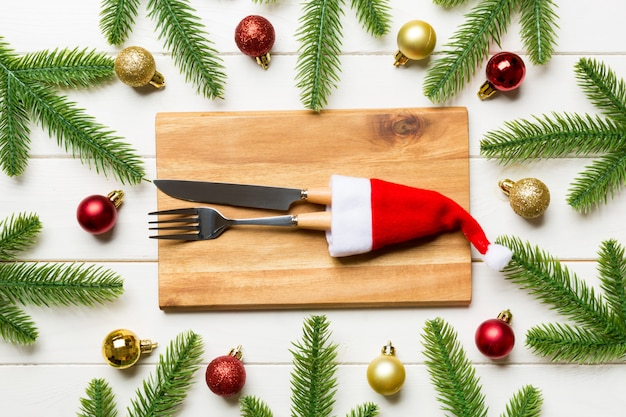 Top view fork, knife and plate surrounded  fir tree and christmas decoratoins on wooden .   eve and holiday dinner