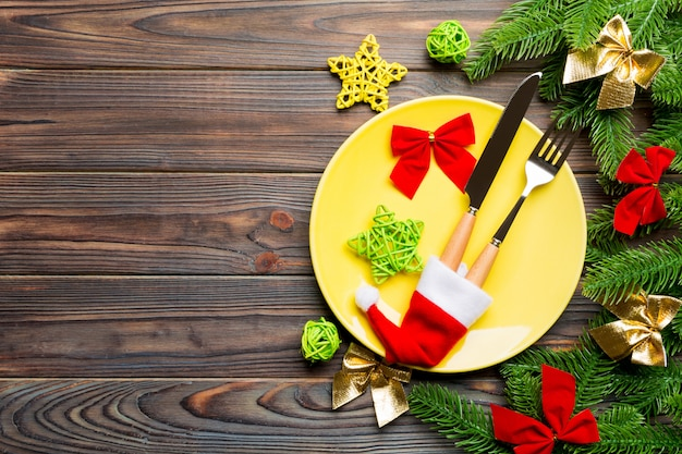 Top view of fork, knife and plate surrounded with fir tree and christmas decorations on wooden background.