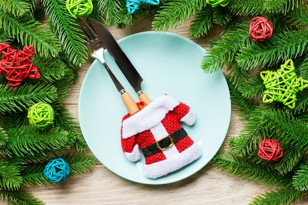 Top view of fork, knife and plate surrounded with fir tree and christmas decoratoins on wooden background. new year eve and holiday dinner concept.