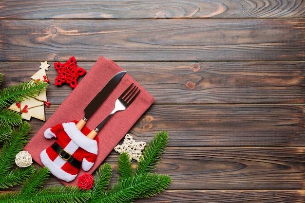 Top view of fork and knife put in santa clothes on napkin with christmas decorations and new year tree