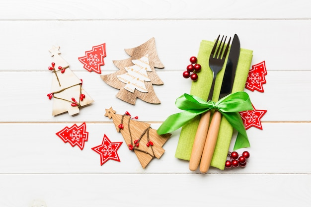 Top view of fork and knife tied up with ribbon on napkin. close up of christmas decorations and new year tree. happy holiday concept
