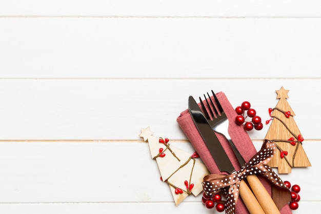 Top view of fork and knife tied up with ribbon on napkin on wooden surface