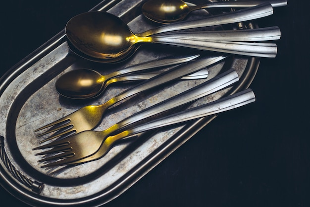 Top view fork and spoon on a silver vintage tray