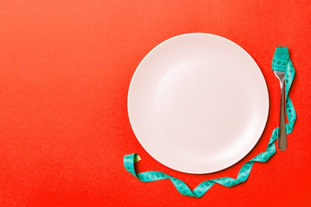 Top view of fork with measure tape near round plate on red background. weight loss concept with empty space for your idea