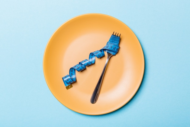 Top view of fork with measure tape in round plate on blue background. weight loss concept with empty space for your idea