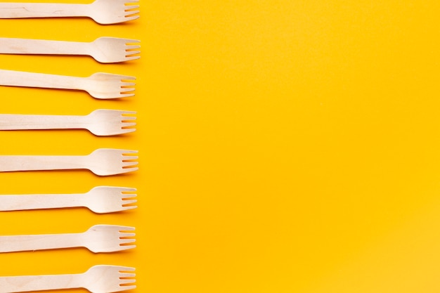 Top view forks arrangement on yellow background