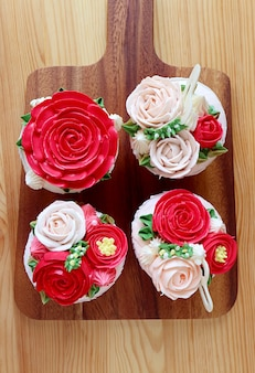 Top view of four beautiful flower shaped frosting cupcakes on wooden background