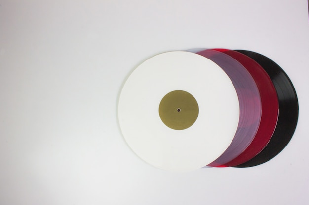 Top view of four vinyls, black, red, blue and white, on white.