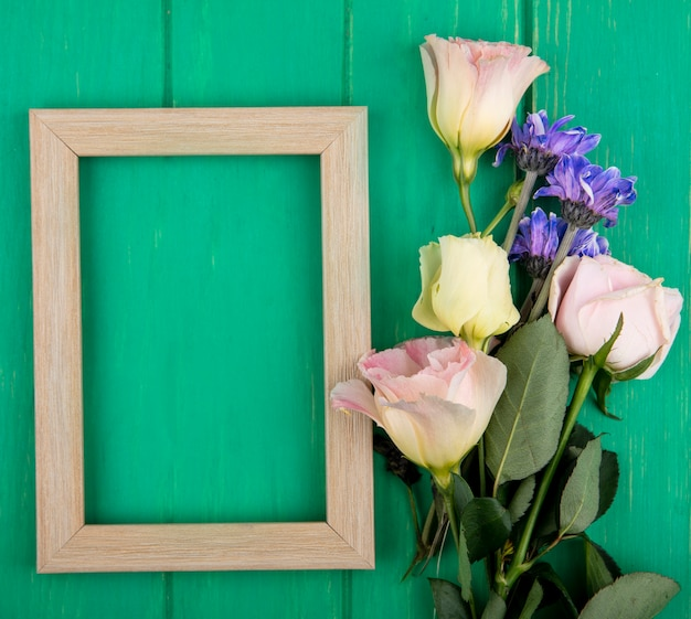 Top view of frame and flowers on green background with copy space
