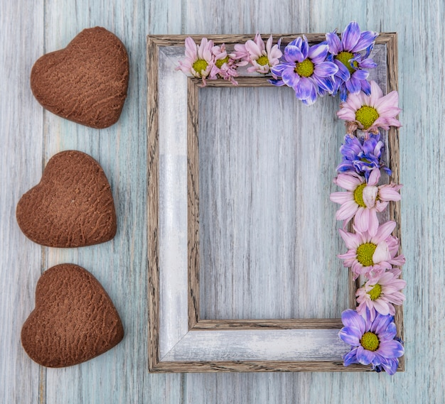 Top view of frame and flowers on it and heart-shaped cookies on wooden background with copy space