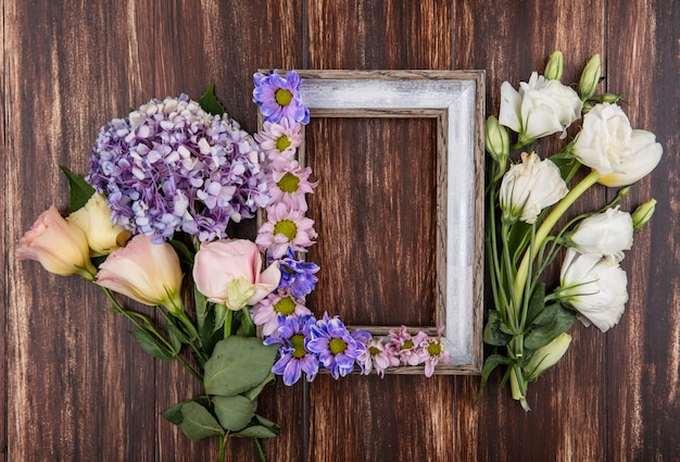 Top view of frame and flowers on it and on wooden background with copy space