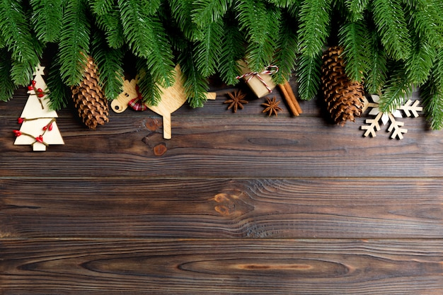 Top view of frame made of fir tree branches and holiday decorations on wooden background. christmas concept with empty space for your design
