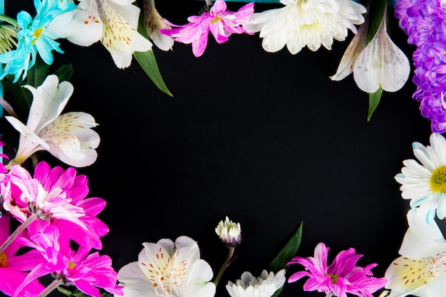 Top view of a frame made of white color alstroemeria flowers with pink and white color chrysanthemum flowers on black background with copy space