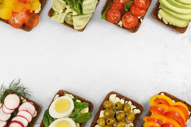Top view frame of open faced vegetarian sandwiches on stone background. vegetables sandwiches with cheese feta. homemade open sandwiches for breakfast. healthy food menu.