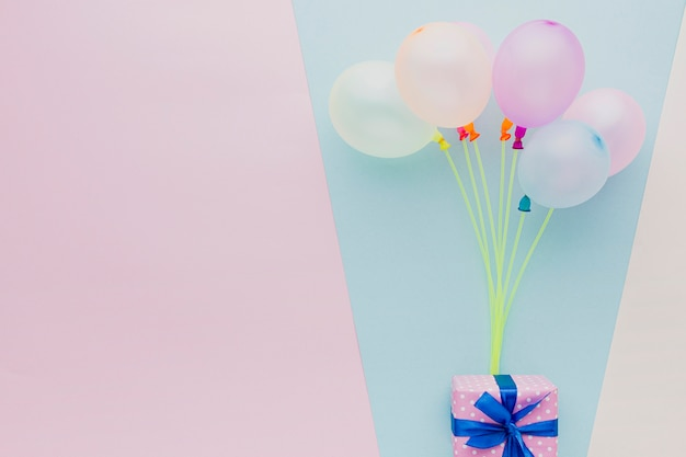 Top view frame with colorful balloons and gift