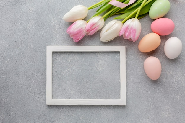 Top view of frame with colorful easter eggs and beautiful tulips