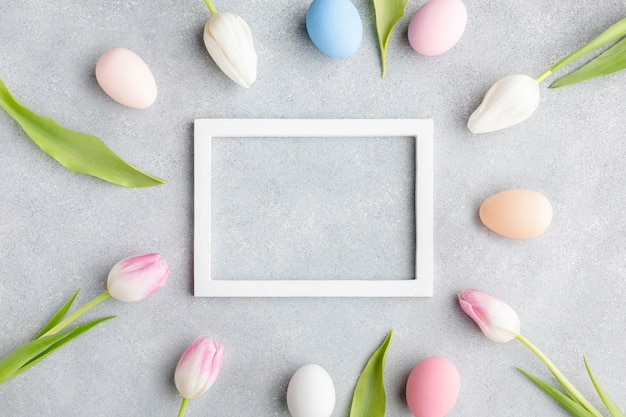 Top view of frame with colorful easter eggs and tulips