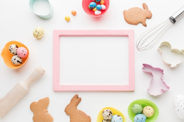 Top view of frame with easter bunny cookies and kitchen utensils