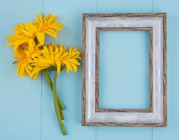 Top view of frame with flowers on blue with copy space