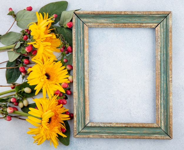 Top view of frame with flowers on white with copy space