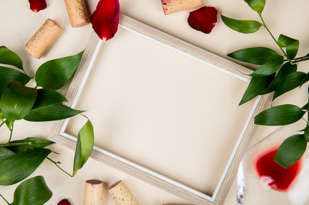 Top view of frame with glass of red wine and corks around on white decorated with leaves and flower petals with copy space 1