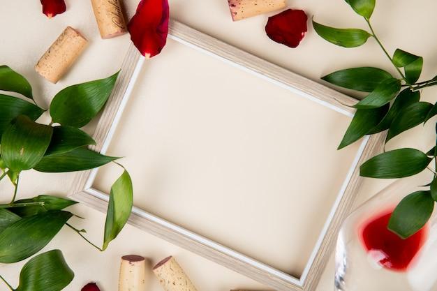 Vista superiore del telaio con bicchiere di vino rosso e tappi intorno su bianco decorato con foglie e petali di fiori con copia spazio 1