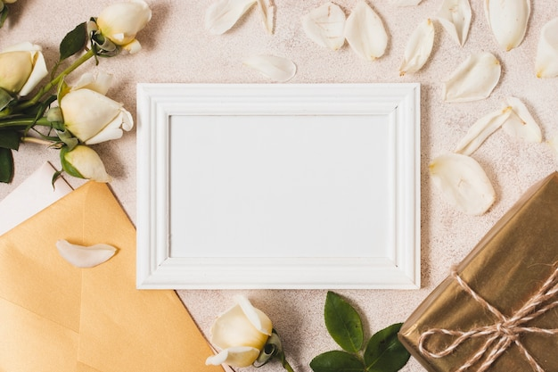 Top view of frame with rose petals and gift
