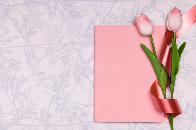 Top view frame with tulips and notebook