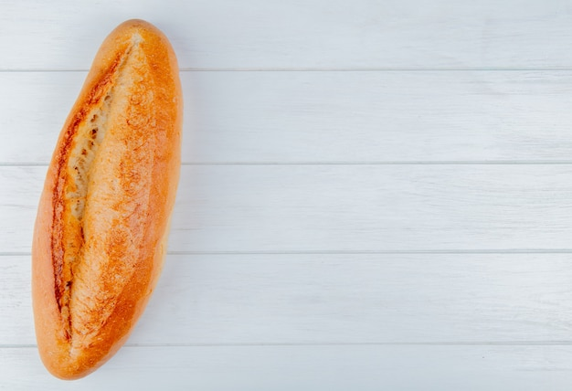 Top view of french baguette on wooden background with copy space