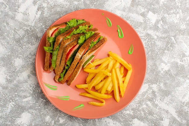 Top view of french fries along with sandwiches inside peach plate