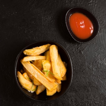 Vista dall'alto di patatine fritte in una ciotola con salsa ketchup