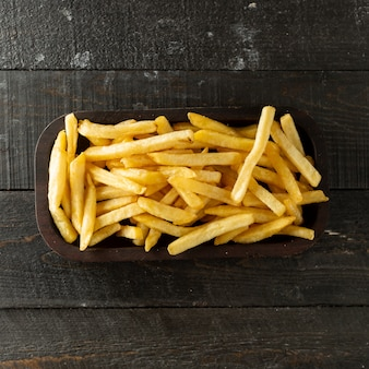 Top view of french fries bowl on wooden surface
