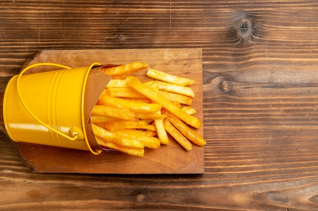 Top view of french fries on brown table