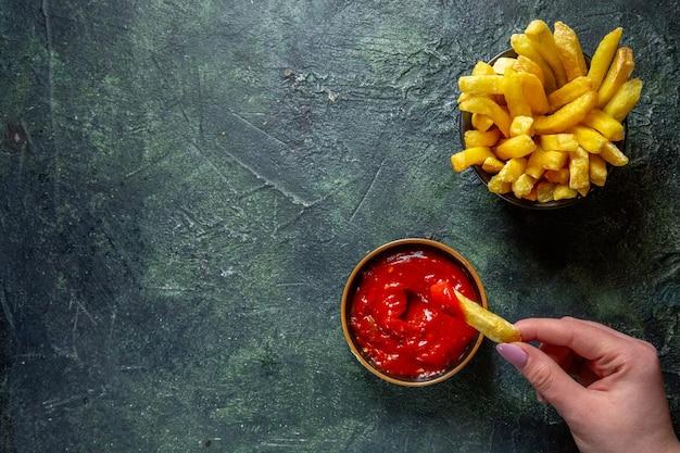 暗い表面で女性がケチャップで食べるフライドポテトの上面図