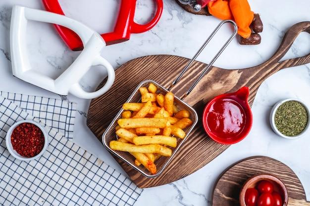 Вид сверху картофель фри в корзине с кетчупом на доске