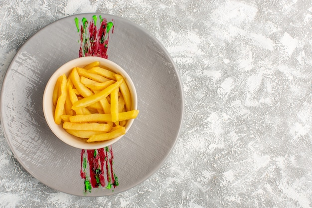 Top view of french fries inside little white plate on the grey light surface