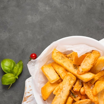 Top view of french fries on plate with herbs and copy space