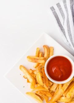 Vista dall'alto di patatine fritte sulla piastra con ketchup e copia spazio