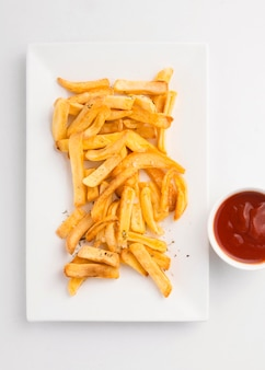 Top view of french fries on plate with ketchup sauce
