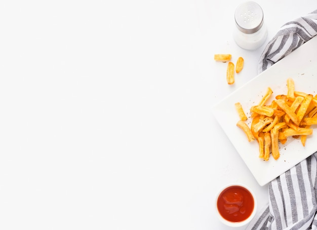 Top view of french fries on plate with ketchup