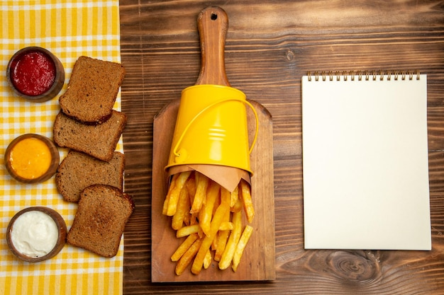 Top view of french fries with bread and seasonings on brown table