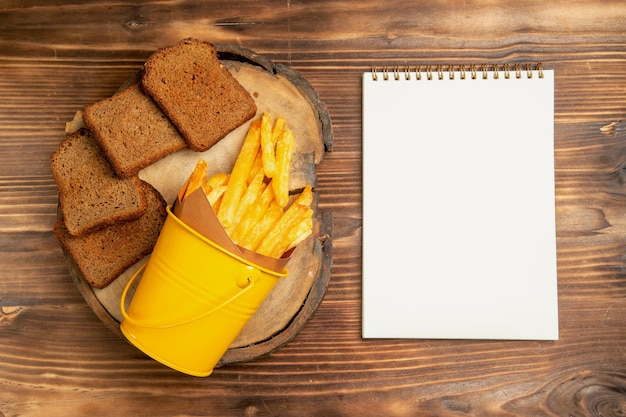 Top view of french fries with dark bread on brown table