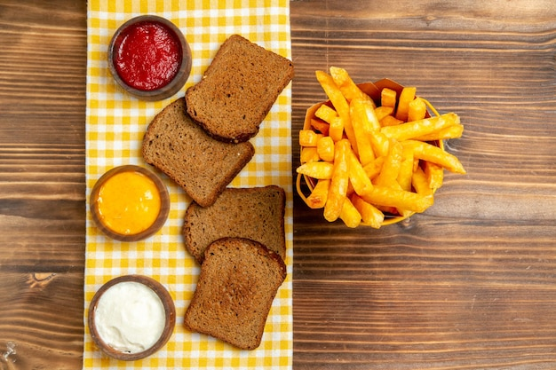 Top view of french fries with dark bread loafs on brown table potato bread meal burger food
