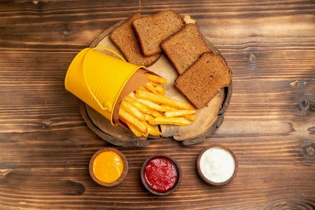 Vista dall'alto di patatine fritte con pane scuro e condimenti sul tavolo marrone
